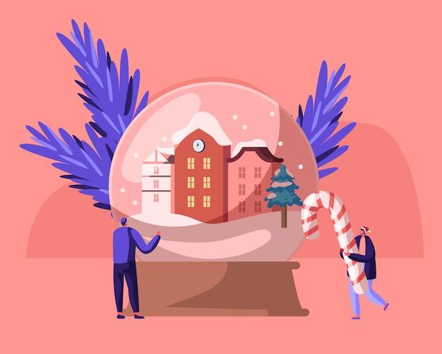 Vacanze di natale e capodanno. piccoli personaggi con simboli di natale enorme globo di cristallo con case di città innevate del fumetto illustrazione piatta