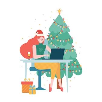 Internet party di natale online. celebrazione del nuovo anno in modalità quarantena. ragazza con un cappello da babbo natale e un bicchiere di champagne è seduta con un laptop vicino all'albero di natale. evento festivo da remoto a casa