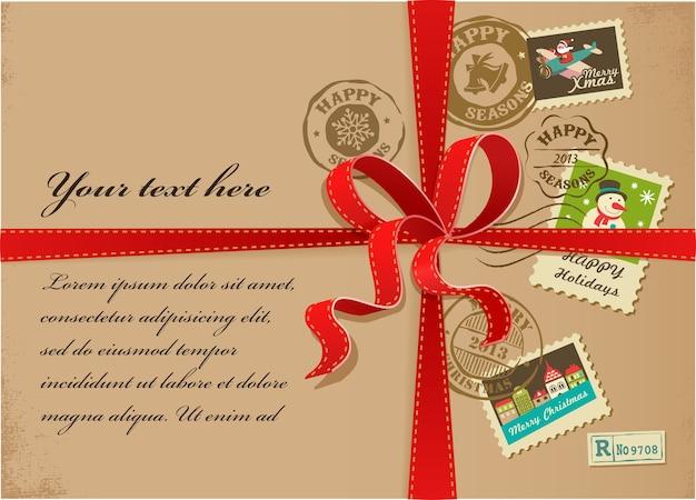 Scatola regalo di natale con nastri rossi di francobolli colorati