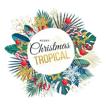Banner rotondo di natale con foglie verdi tropicali e decorazioni natalizie.