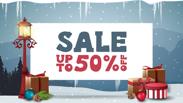 Saldi di natale, fino a 50, banner sconto con foglio di carta bianco con offerta, lanterna a palo, regali e paesaggio invernale blu
