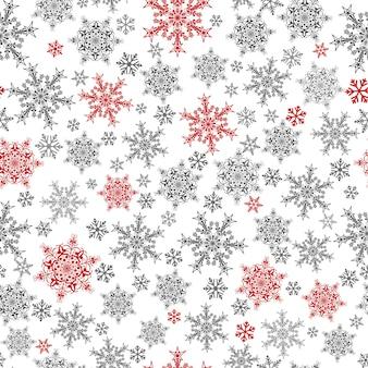 Modello senza cuciture di natale di fiocchi di neve grandi e piccoli, rossi e grigi su bianco