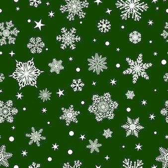 Reticolo senza giunte di natale di fiocchi di neve grandi e piccoli, bianco su verde
