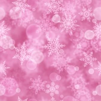 Reticolo senza giunte di natale di fiocchi di neve sfocati su sfondo rosa
