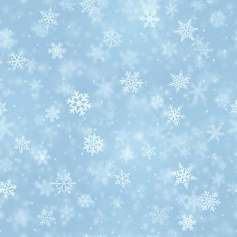 Modello senza cuciture natalizio di complessi fiocchi di neve che cadono sfocati e chiari in colori blu chiaro con effetto bokeh
