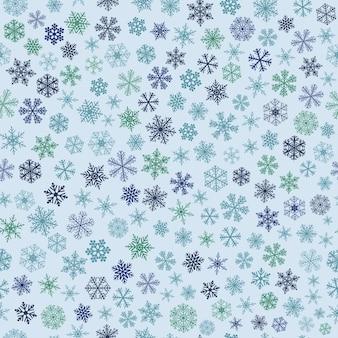Reticolo senza giunte di natale di piccoli fiocchi di neve, blu e verde su azzurro