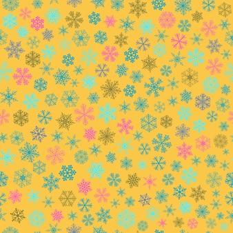 Reticolo senza giunte di natale di piccoli fiocchi di neve, azzurro e rosa su giallo