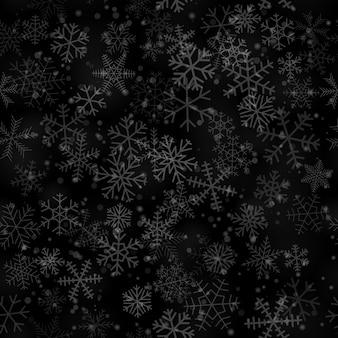 Modello senza cuciture natalizio di fiocchi di neve di diverse forme, dimensioni e trasparenza, su sfondo nero