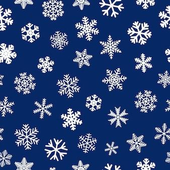 Reticolo senza giunte di natale di fiocchi di neve, bianco su sfondo blu