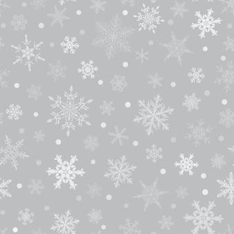 Reticolo senza giunte di natale dei fiocchi di neve, bianco su sfondo grigio.