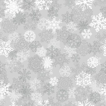 Reticolo senza giunte di natale di fiocchi di neve, bianco su grigio