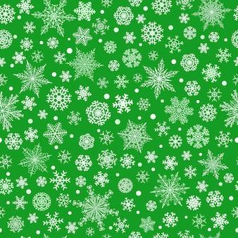 Modello senza cuciture di natale di vari fiocchi di neve grandi e piccoli complessi, bianchi su sfondo verde