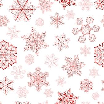 Modello senza cuciture di natale con fiocchi di neve rossi grandi e piccoli su sfondo bianco