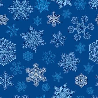 Modello senza cuciture di natale con fiocchi di neve grandi e piccoli su sfondo blu