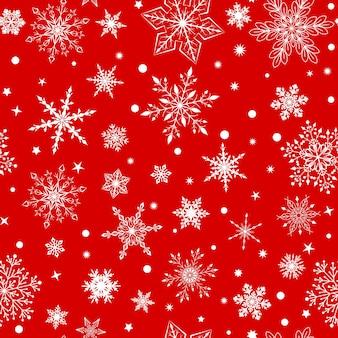 Modello senza cuciture di natale con vari fiocchi di neve grandi e piccoli complessi, bianchi su sfondo rosso