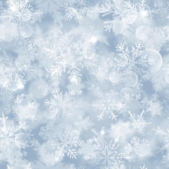 Modello senza cuciture di natale con fiocchi di neve sfocati bianchi, riflessi e scintillii su sfondo azzurro