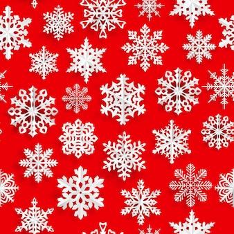 Reticolo senza giunte di natale con fiocchi di neve di carta bianca su sfondo rosso