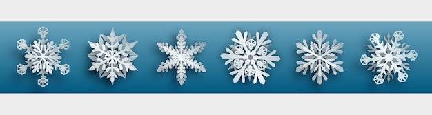 Set natalizio di fiocchi di neve di carta bianchi complessi con ombre morbide su sfondo azzurro