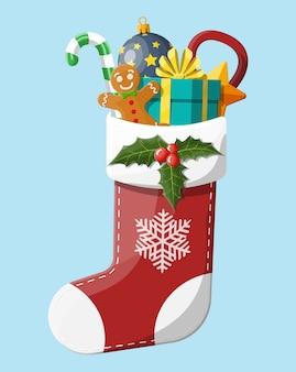 Calza natalizia con agrifoglio, confezione regalo, omino di marzapane, bastoncino di zucchero con pallina di vetro. felice anno nuovo decorazione. buon natale vacanza. celebrazione del nuovo anno e del natale.