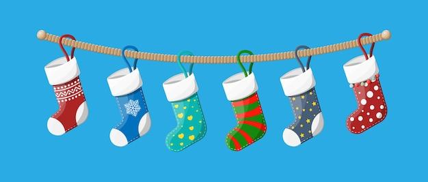 Calze natalizie in vari colori su corda. set di calzini di stoffa natalizia. appendere decorazioni natalizie per regali. celebrazione del nuovo anno e del natale.