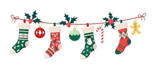 Calze natalizie con ornamenti tradizionali per le feste, palline decorative, omino di pan di zenzero. elementi di abbigliamento per bambini appesi con motivi natalizi su corda. calzini con fiocchi di neve, pupazzo di neve, albero di natale