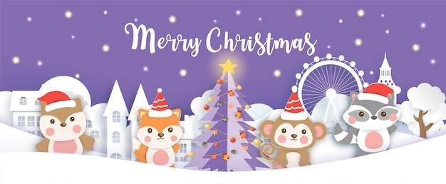 Natale con simpatici animali nel villaggio di neve tagliato con carta e stile artigianale.
