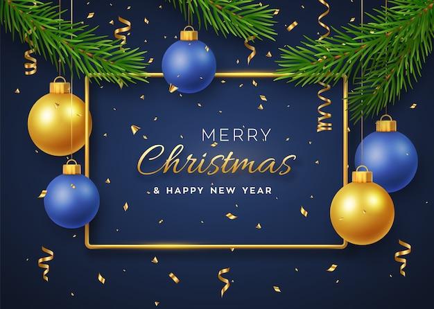 Natale con palline dorate e blu lucenti pendenti, cornice metallica dorata e rami di pino.