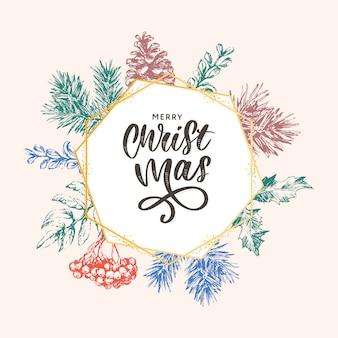 Christmaslettering con cornice dorata e rami di albero di natale.