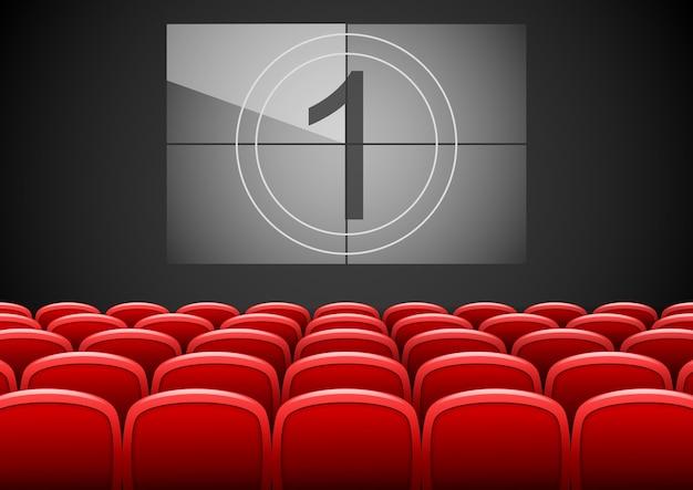 Cinema auditorium con sedili rossi e schermo cinematografico