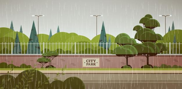 Cartello del parco della città sulle gocce di pioggia del recinto che cadono orizzontale piovoso del fondo del paesaggio di giorno di estate