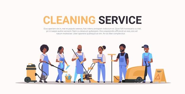 Squadra di addetti alle pulizie in uniforme che lavorano insieme concetto di servizio di pulizia bidelli di sesso femminile di sesso maschile utilizzando lo spazio di copia orizzontale integrale di attrezzature professionali