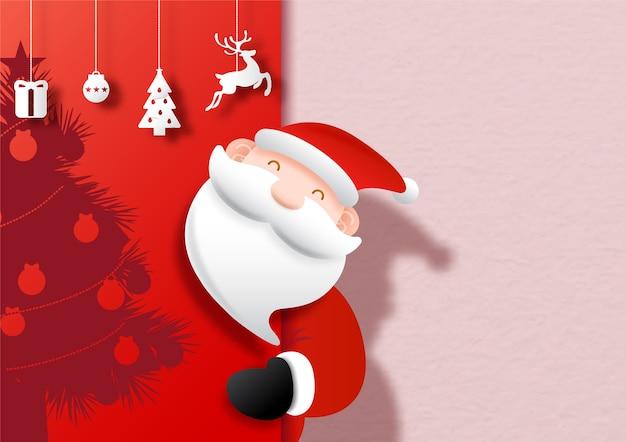 Primo piano santa con oggetti simbolo delle vacanze di natale appendere sulla sagoma a metà dell'albero di natale e rosa, sfondo rosso.