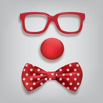 Accessori da clown isolati su sfondo grigio, occhiali da clown, naso e farfallino a pois.
