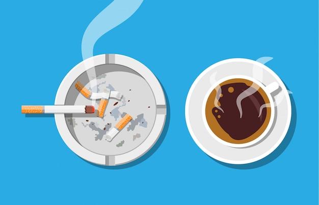 Tazza di caffè e posacenere pieno di sigarette fumi.