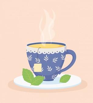 Tempo e tè del caffè, tazza con la bustina di tè e foglie di menta sul piatto