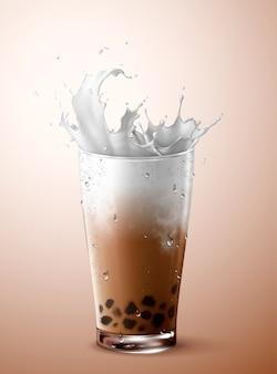 Tè freddo a bolle con schizzi di latte in tazza di vetro