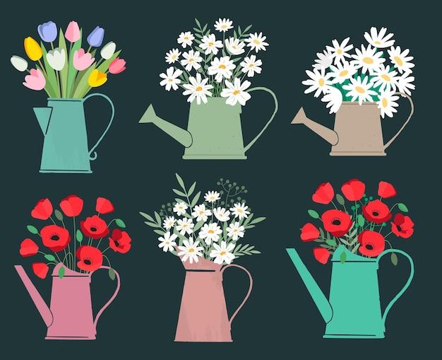 Raccolta di vari tipi di fiori che sbocciano disposti in annaffiatoi colorati