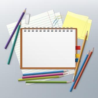 Matite colorate con blocco note, clip, fogli di carta e spazio per il testo
