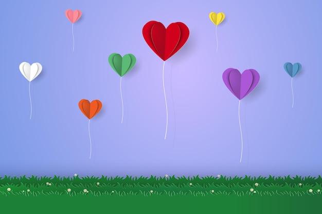 Palloncini colorati piegati a cuore che sorvolano l'erba in stile arte cartacea