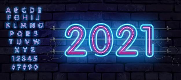Banner al neon colorato 2021 banner. tabellone per le affissioni al neon luminoso realistico su un muro di mattoni. il concetto di un biglietto di auguri con un testo luminoso. l'alfabeto neon del 2021.