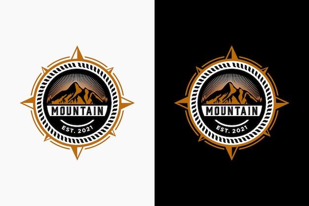 Bussola e montagna per l'ispirazione per il design del logo di avventura di viaggio