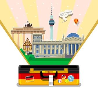 Concetto di viaggio in germania o di studio della bandiera tedesca tedesca con punti di riferimento in valigia aperta illustrazione vettoriale di design piatto