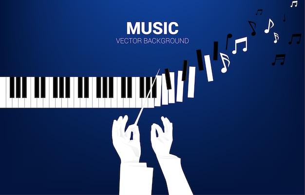 La mano del direttore d'orchestra con la chiave del pianoforte si trasforma in una nota musicale. concetto di sfondo per eventi di canzoni classiche e festival di musica