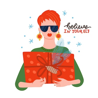 Ragazza fresca che indossa occhiali da sole e palline come orecchini con scatola regalo di natale nelle mani festività natalizie...