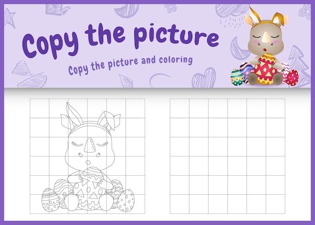 Copia l'immagine del gioco per bambini e la pagina da colorare a tema pasqua con un simpatico rinoceronte usando fasce con orecchie da coniglio che abbracciano le uova