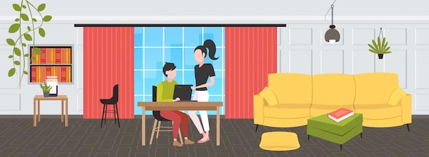Coppia di uomini d'affari utilizzando il computer portatile sul posto di lavoro scrivania uomo d'affari con assistente femminile brainstorming lavorando insieme concetto di lavoro di squadra moderno ufficio interno orizzontale piena lunghezza