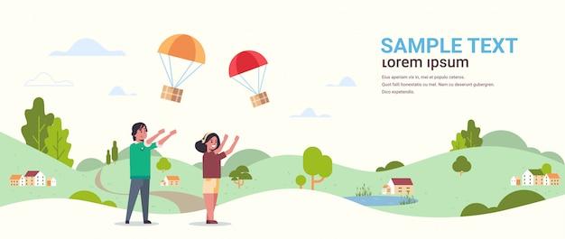 Coppia che cattura la scatola del pacco che cade con il paracadute dal cielo pacchetto di spedizione posta aerea espresso paesaggio della campagna di consegna postale