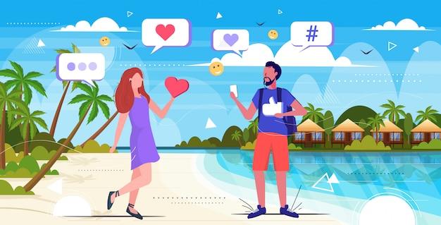 Coppia avendo le vacanze estive utilizzando l'app mobile online concetto di dipendenza digitale rete di social media app uomo donna che cammina sulla spiaggia paesaggio marino sfondo schizzo completo lunghezza orizzontale