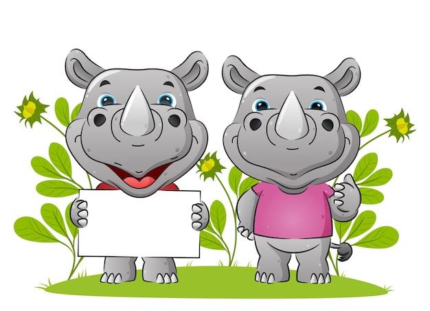 La coppia di rinoceronti tiene in mano il tabellone bianco e dà l'illustrazione del pollice in su