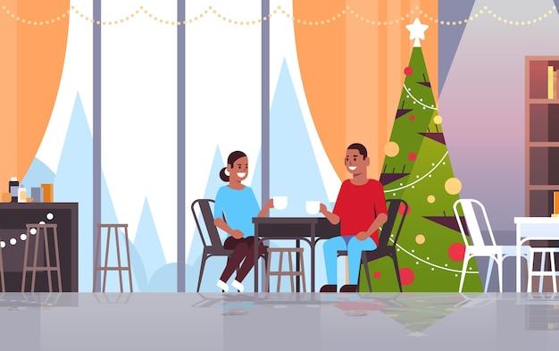 Coppia seduta al tavolo del bar a bere caffè e discutere durante la riunione buon natale felice anno nuovo concetto di vacanze moderno ristorante interno
